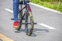 Mini trick stunt bike with camouflage fat tires and pegs being ridden by guy in red tennis shoes and blue jeans on paved surface. Cropped and motion blur stock images