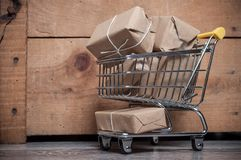 Mini trolley full of parcels to send on wooden backgr Stock Photos