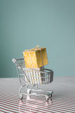 Mini trolley with gold christmas present Royalty Free Stock Photos
