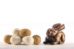 Mini truffle Easter eggs with carved netsuke Easter bunny rabbit. Traditional carved netsuke rabbit representing the Easter bunny alongside a pile of mini Easter Royalty Free Stock Photo