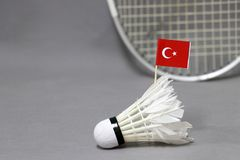 Mini Turkey flag stick on the white shuttlecock on the grey background and out focus badminton racket. Concept of badminton sport royalty free stock image
