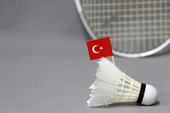 Mini Turkey flag stick on the white shuttlecock on the grey background and out focus badminton racket. Concept of badminton sport royalty free stock images