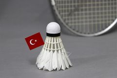 Mini Turkey flag stick on the white shuttlecock on the grey background and out focus badminton racket. Concept of badminton sport stock photos