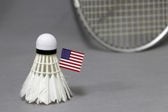 Mini United state of America flag stick on the white shuttlecock on the grey background and out focus badminton racket. Concept of badminton sport royalty free stock photography