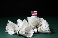 Mini United States of America flag stick on the heap of used shuttlecocks on green floor of Badminton court. With dark black background royalty free stock image