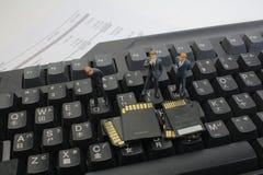 Mini uomini di affari da pensare esaminando la scheda di memoria Fotografia Stock Libera da Diritti