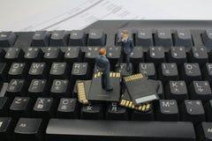 Mini uomini di affari da pensare esaminando la scheda di memoria Fotografie Stock