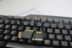 Mini uomini di affari da pensare esaminando la scheda di memoria Immagine Stock