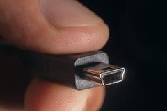 Mini- USB för handinnehavsvart kabel Mannens hand rymmer ett USB kortkortkontaktdon Arkivbilder