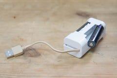 Mini-USB-Ladegerät für wieder aufladbares AA/AAA Ni-Mh und Ni-CD-Batterien auf einer Holzoberfläche Stockbild