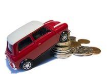 Mini véhicule rouge de jouet contre la pile des pièces de monnaie britanniques Images stock
