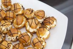 Mini- vaniljeclairbollar med chokladsås Royaltyfri Bild