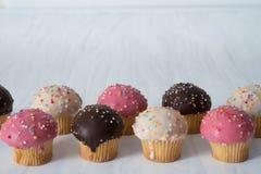 Mini Vanilla Cupcakes in der Linie auf Tabelle Stockbild