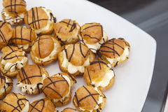 Mini vanilla eclair balls with chocolate sauce. Royalty Free Stock Image