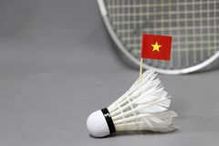 Mini Vietnam flag stick on the white shuttlecock on the grey background and out focus badminton racket. Concept of badminton sport stock photography