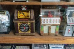 Mini vintage retro jukebox music machine in wooden shelf display stock images