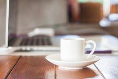 Mini witte koffiekop op werkplek Stock Foto