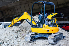 Mini yellow excavator on a construction site royalty free stock photos