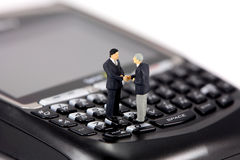Mini zakenlieden op cellphone stock fotografie