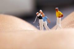 Miniabbildungen, die Golf spielen Lizenzfreie Stockfotografie