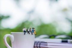 Miniatur-businessmans, die Buch auf dem Tasse Kaffee readinging sind Stockbild