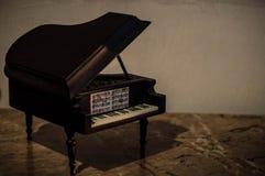 Miniatur des Klaviers mit Papieren von Musik Stockfotos