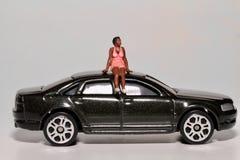 Miniatur einer schwarzen Frau, die auf dem Dach eines Autos sitzt Stockfotos