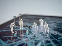Miniatur forensic people examining broken tablet screen royalty free stock photography