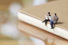 Miniatur2 menschen, die gelesene Zeitung auf Anmerkungsbuch unter Verwendung als Hintergrundgeschäftskonzept sitzen lizenzfreie stockfotografie