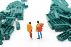 Miniatur2 menschen stehen auf dem Gehweg sind ein Block des grünen Dschungels oder der Wiese Bedeutet den Anfang der Reise, um da Stockbilder