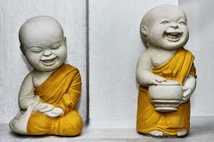 Two happy monks miniatures at a buddhist temple royalty free stock photography