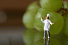 Miniatura de um cozinheiro chefe com uvas Imagens de Stock