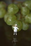 Miniatura de um cozinheiro chefe com uvas Fotografia de Stock Royalty Free