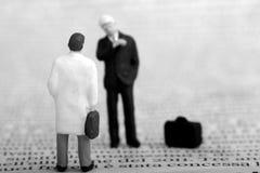 Miniatura degli uomini d'affari su un giornale Immagine Stock