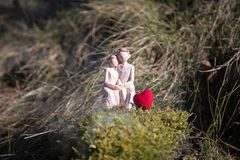 Miniatura dell'donne e un uomo nell'amore che si siede sul banco del segno del cuore con il copyspace leggero del bokeh, sulle co fotografia stock