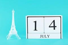 Miniatura della torre Eiffel e del calendario di legno su un fondo blu Il concetto della festa è il 14 luglio, il giorno della ra Fotografie Stock
