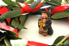 Miniatura dello studente di graduazione su fondo bianco, corona verde dell'alloro Fotografie Stock Libere da Diritti