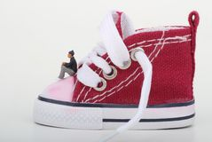 Miniatura di un ragazzo che si siede su una scarpa da tennis Immagini Stock Libere da Diritti