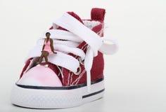 Miniatura di un ragazzo che si siede su una scarpa da tennis Immagini Stock