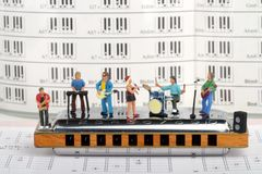 Miniatura di una banda rock che gioca sull'armonica immagine stock libera da diritti