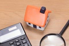 Miniatura dom wśród kalkulatora z magnifier obrazy royalty free