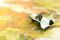 A miniatura, negócios team o assento na asa do avião para o curso em todo o mundo Fotografia de Stock