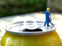 Miniaturarbeiter, der schweren Benzinkanister auf Getränkedose trägt Stockfotografie