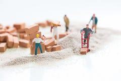 Miniaturarbeiter, die Bauarbeit mit Ziegelsteinen und Sandhintergrund erledigen Lizenzfreies Stockfoto