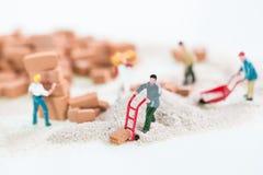 Miniaturarbeiter, die nahes hohes der Bauarbeit tun Lizenzfreie Stockfotos