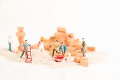 Miniaturarbeiter, die nahes hohes der Bauarbeit tun Lizenzfreies Stockfoto