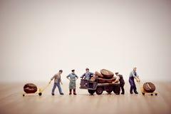 Miniaturarbeitskräfte, die Kaffeebohnen auf LKW laden Lizenzfreie Stockfotografie