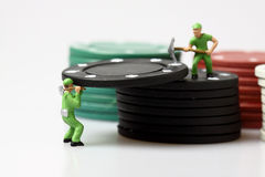 Miniaturarbeitskräfte, die Kasinochips stapeln Stockfotografie
