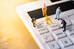 Miniaturarbeitskräfte, die Steuerknopf auf Taschenrechner graben stockfoto