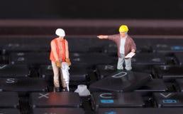 Miniaturarbeitskräfte mit dem Bohrgerät, das an Tastatur arbeitet Lizenzfreie Stockfotografie